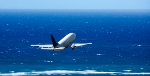 Passenger airplane taking off from airport headed over the Pacific ocean.